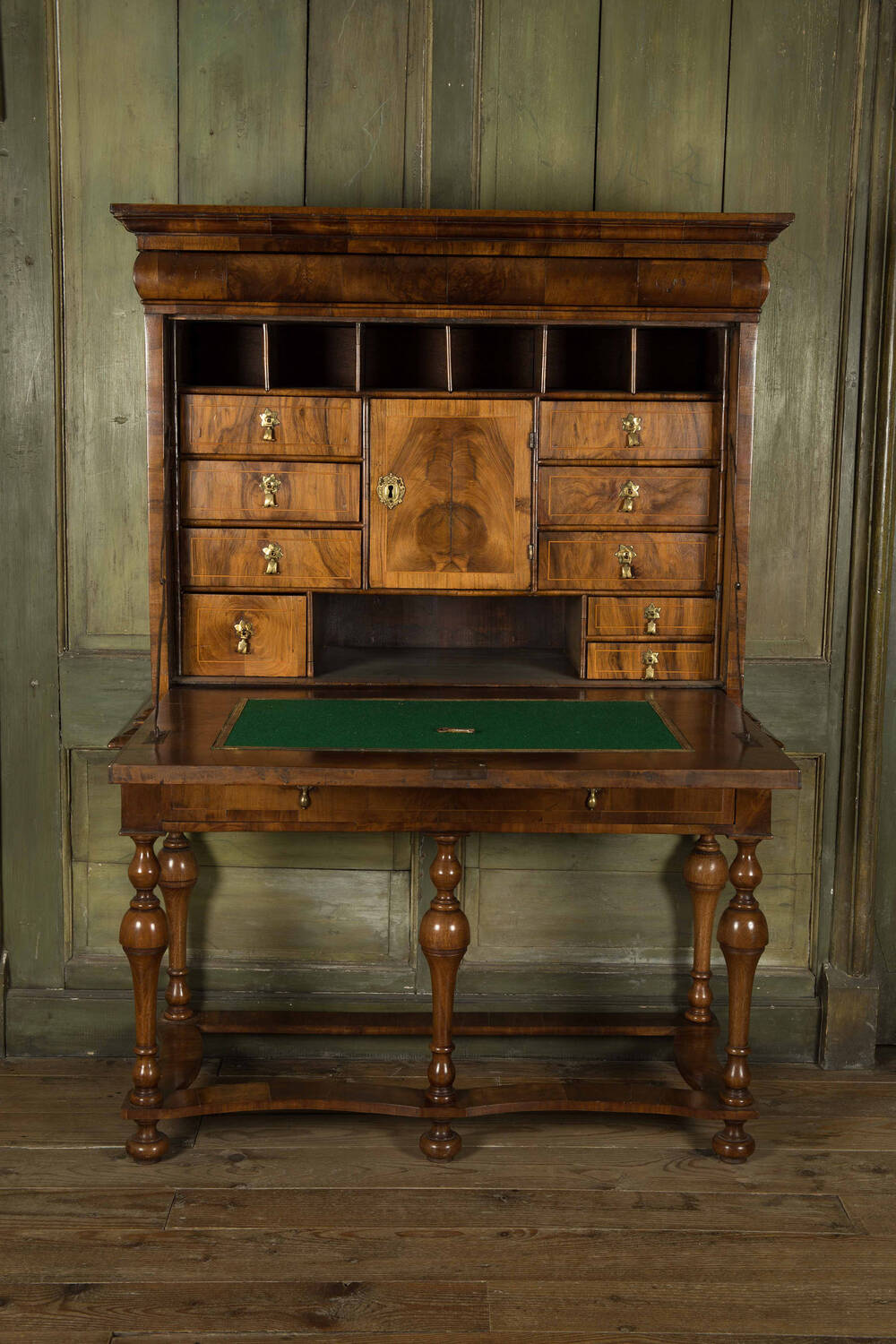 A polished walnut writing desk, opened out to reveal lots of drawers and storage slots inside. The desk has a felted inlay. It has six spindle legs.