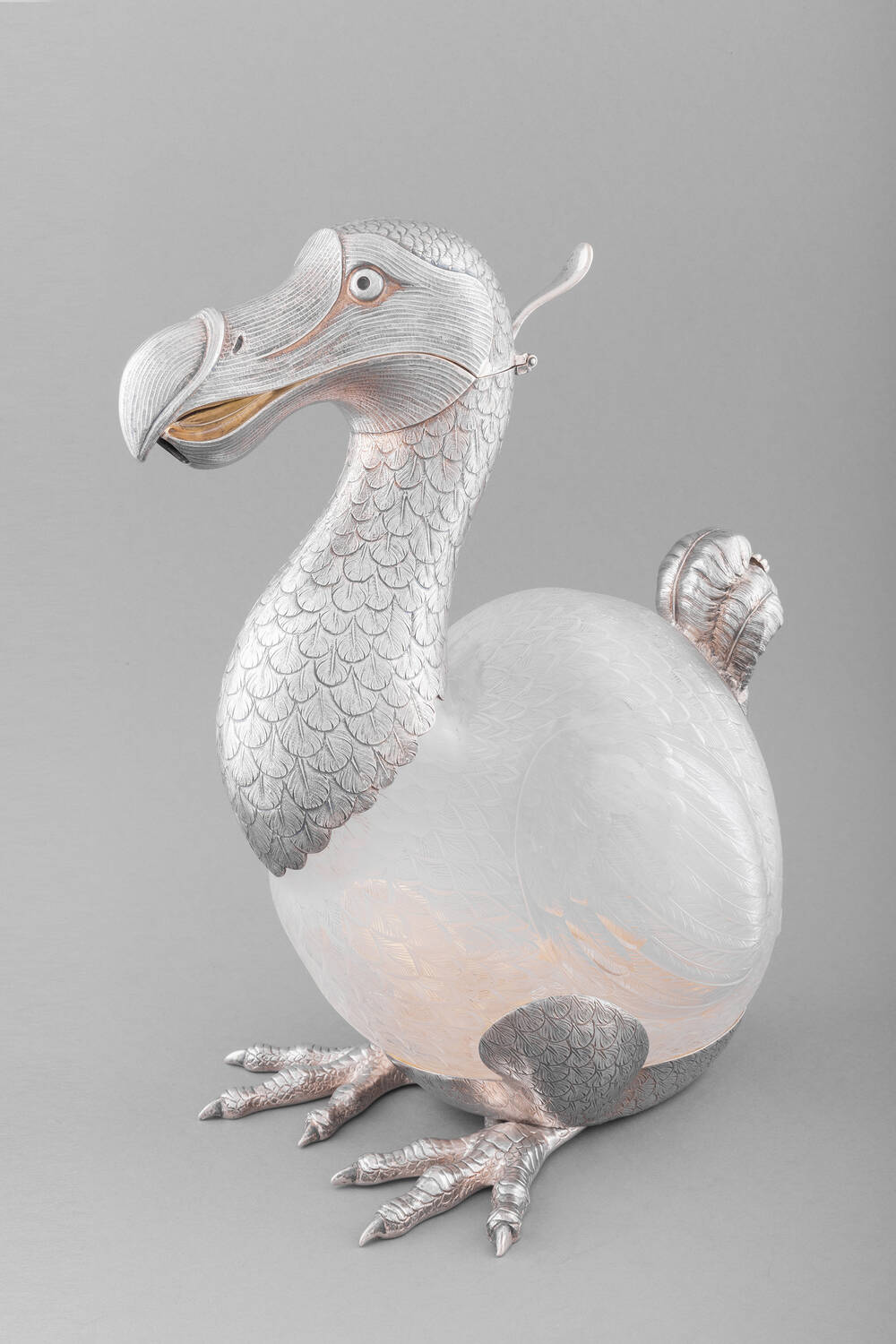 A silver wine jug, shaped like a dodo. The hinged beak opens to pour the wine through.