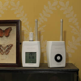 Two environmental monitors sit on a shelf beside some framed butterflies, in Canna House. The wallpaper in the background is yellow with a white leaf pattern.