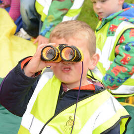A young boy looking through binoculars