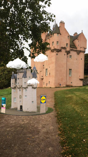 An augmented image of a castle appears on a gravel path, with the real castle in the background. The virtual image has white clouds bobbing over it, and the Lidl logo on a structure next to the castle.
