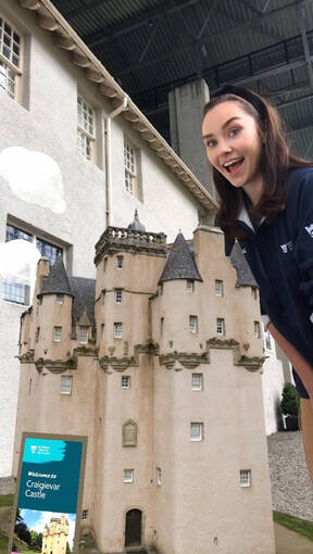 An augmented image of a castle appears on the gravel path in front of the Hill House. A lady stands beside it, smiling.