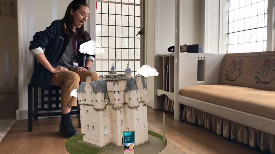 An augmented image of a castle appears on the wooden floor of the parlour at the Hill House. A woman sits on a Mackintosh-designed stool behind it, looking at it in wonder.