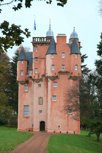 Front view of the pink-walled Craigievar Castle. A gravel path leads to the small front door, with trees at the side. A saltire flag flies from the roof.