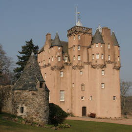 Craigievar Castle alongside the old barmkin wall and outbuilding