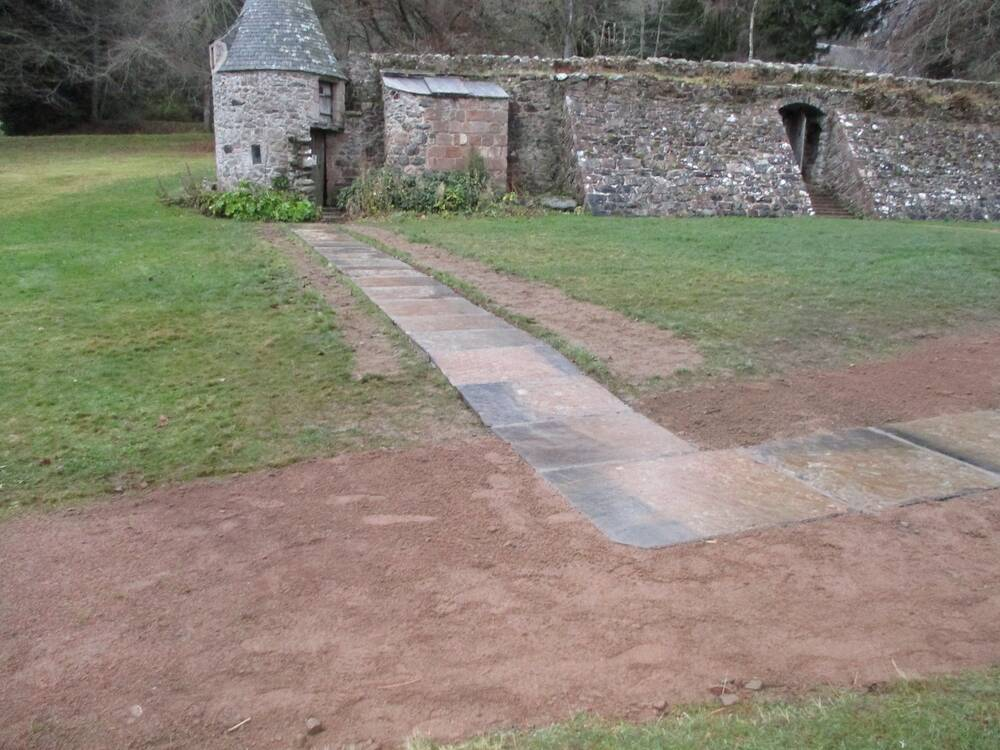A newly paved flagstone path leads out from an old stone wall, with a corner tower. An arched entrance can be seen half way along the old stone wall, with a set of stone stairs.