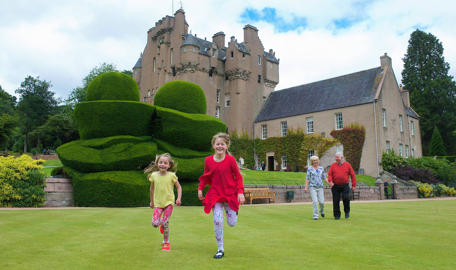 Tow children run towards the camera on the lawn in front of Crathes Castle. An older couple walk hand in hand behind them.