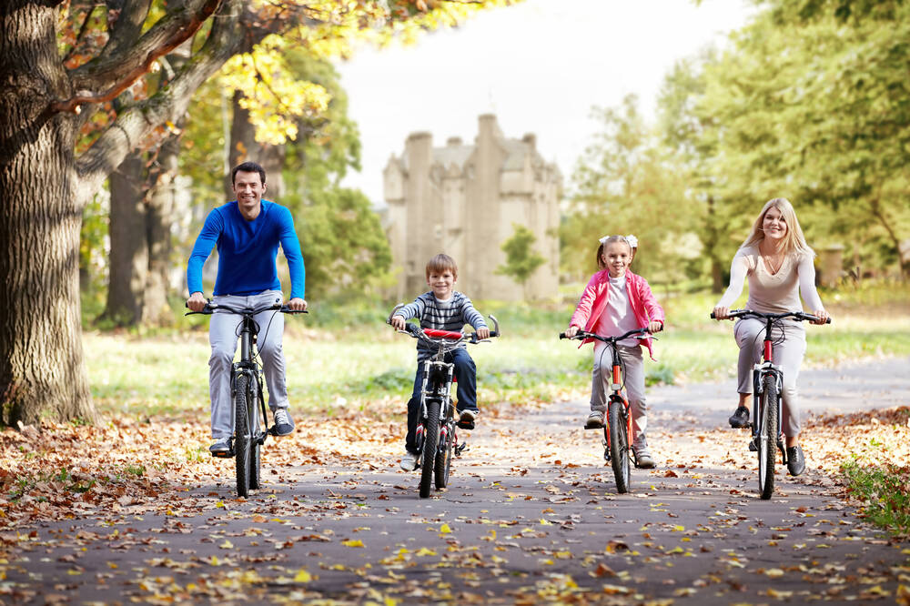 Family cycling through Crathes Castle Estate