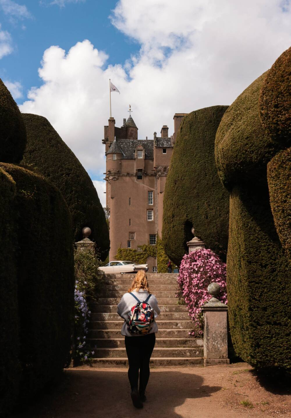 A lady stands with her back to the camera in front of some steps leading to Crathes Castle.