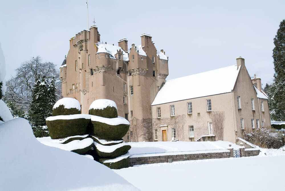 Crathes Castle in winter. The castle is in the background with the roof covered in snow. The yew hedges are in the foreground, covered with a thick layer of snow. as are the garden walls and flowerbeds.
