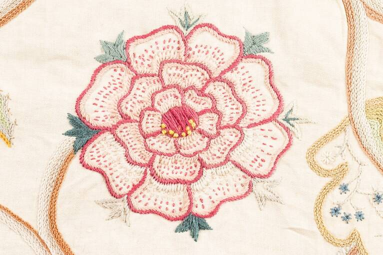 An embroidered rose, mainly with pink stitching, found on the panel at Crathes Castle