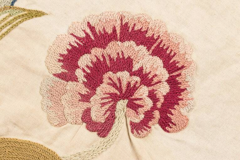 An embroidered carnation in shades of red, pink and cream, found on the panel at Crathes Castle
