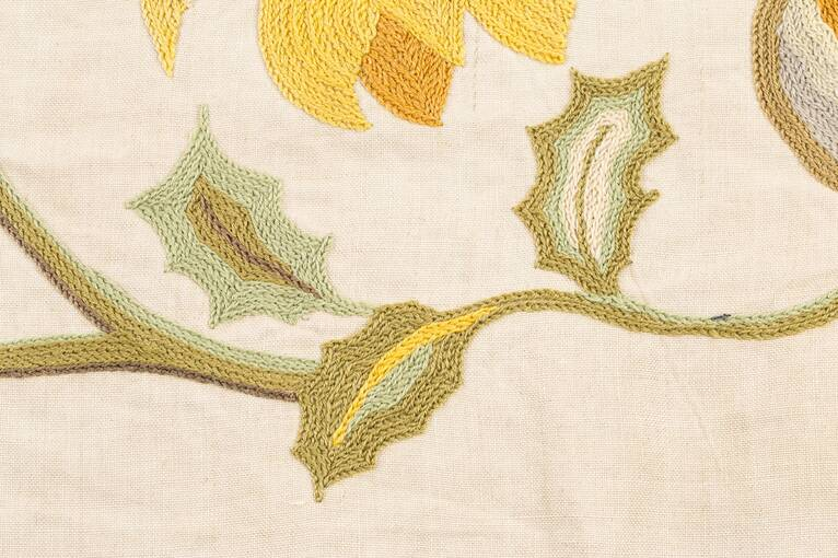 Three embroidered holly leaves on a green stem, with yellow petals at the top of the image.