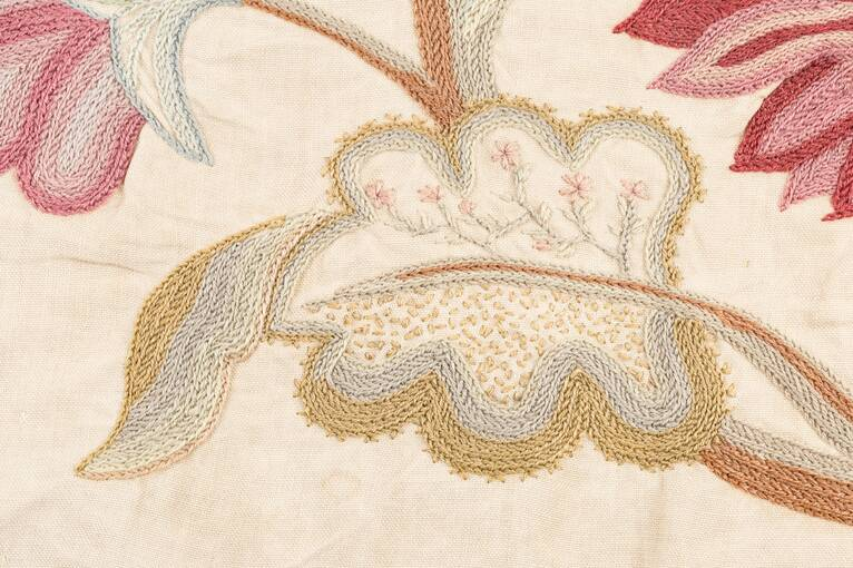An embroidered curling leaf. A variety of stitches are used inside the leaf, some showing delicate pink flowers.