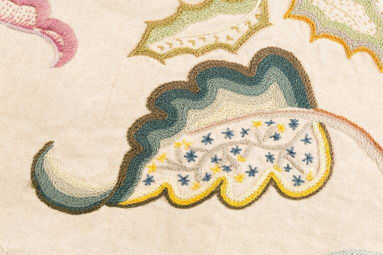An embroidered curling leaf. The top half is filled in with different coloured bands of stitching; the bottom half includes delicate stitched yellow and blue flowers.