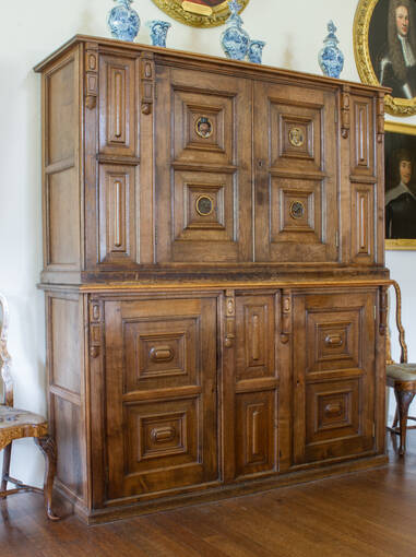 A large wooden cupboard with many doors and drawers in the great hall at Crathes Castle. Many of the panels have small portraits on the front.
