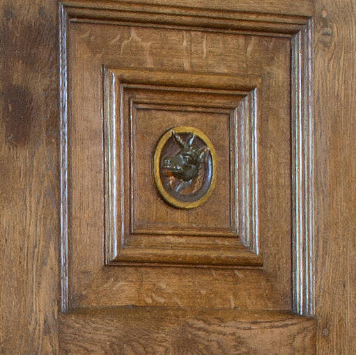 A close-up of the panel on the cupboard that features the unicorn portrait.