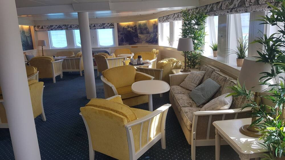 The lounge on the ship, showing soft seating arranged around white circular tables.