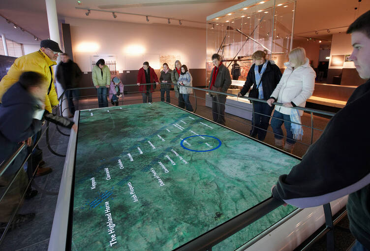Visitors watching a re-enactment of the Battle of Culloden on an interactive map.