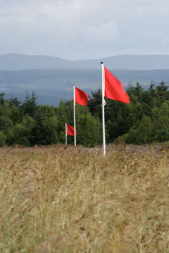 Flag poles with red flags are used on the moor to mark the front line of the government troops.