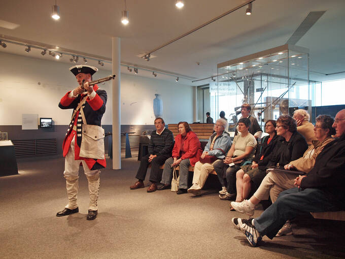 A man dressed in a soldier's uniform shows visitors how a musket works.