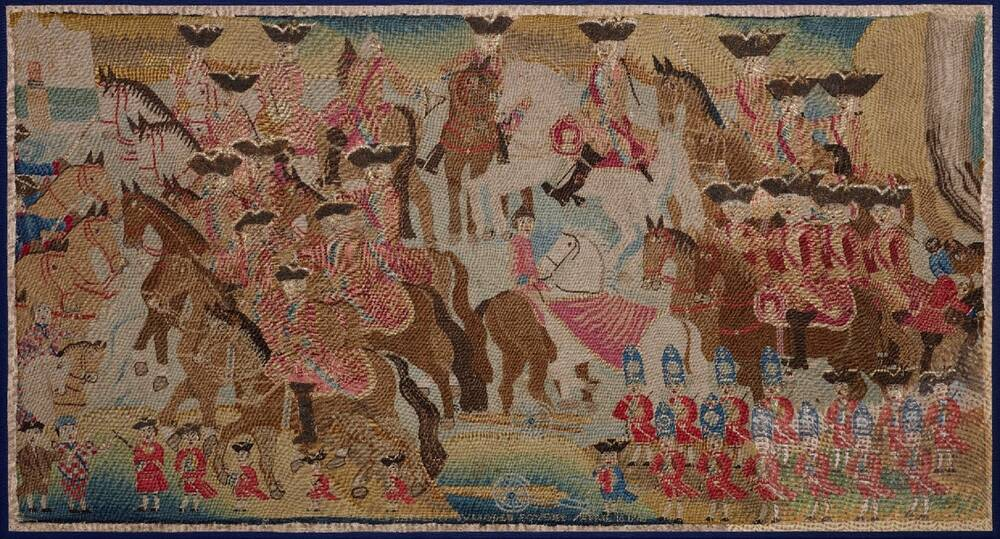 A large embroidered picture, depicting a battle, is displayed against a navy background.