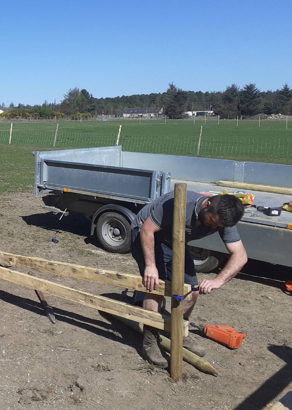 A man builds a fence in a stable area. He is hammering a wooden plank to a wooden post. A large trailer is parked behind him. He wears shorts and a t-shirt, and the sky is bright blue in the background.