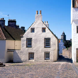 The mercat cross in the cobbled village square in Culross, surrounded by white 17th-century houses.