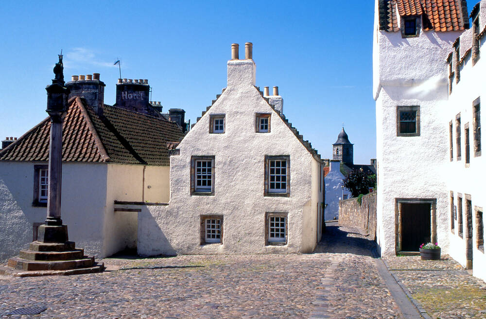 The mercar cross in the village square in Culross, surrounded by cobblestones and 17th-century houses.