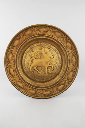 A large golden-looking alms plate with a unicorn standing under a tree at the centre