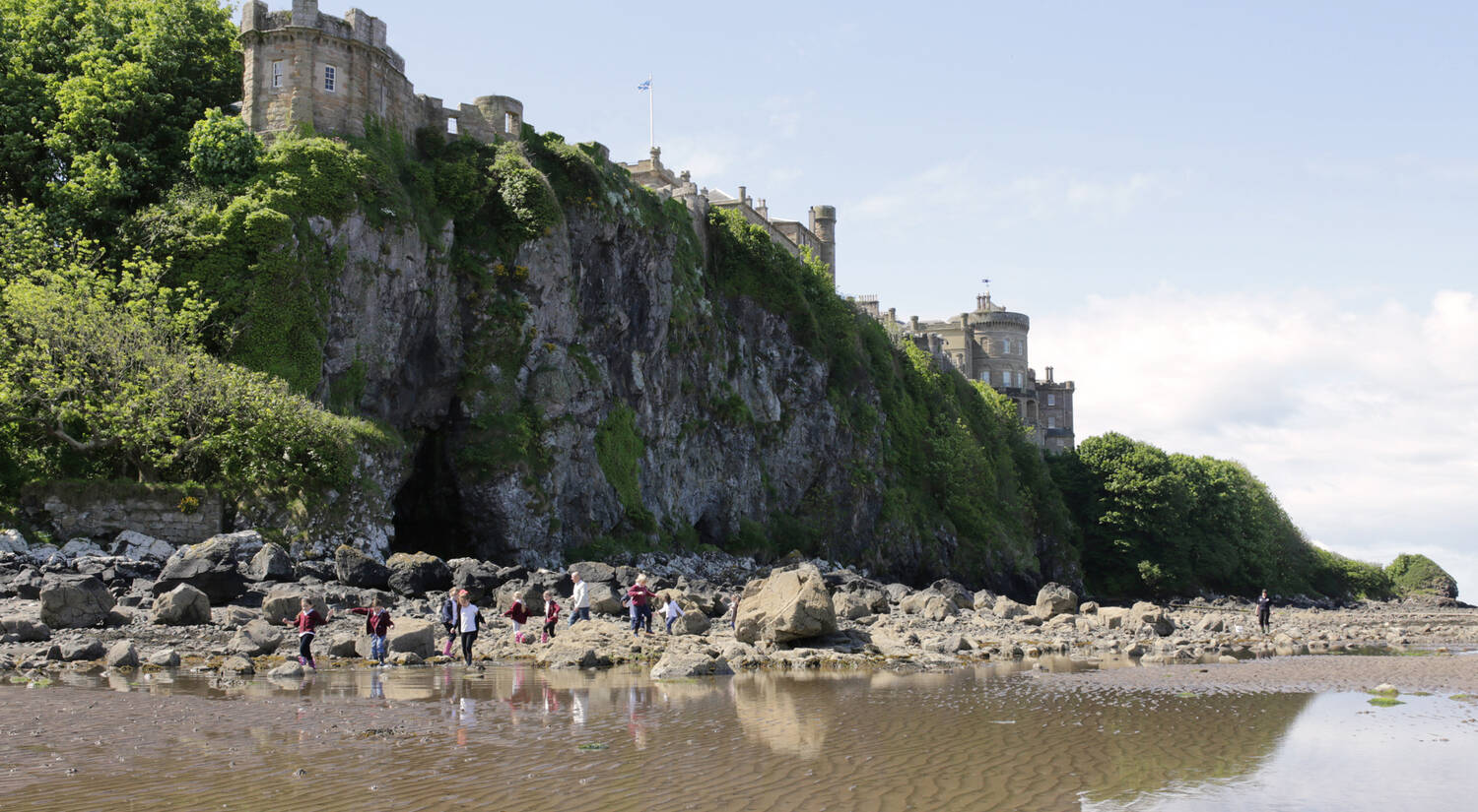 A view of Culzean Castle from the shoreline. Children play in the rockpools surrounded by large boulders.