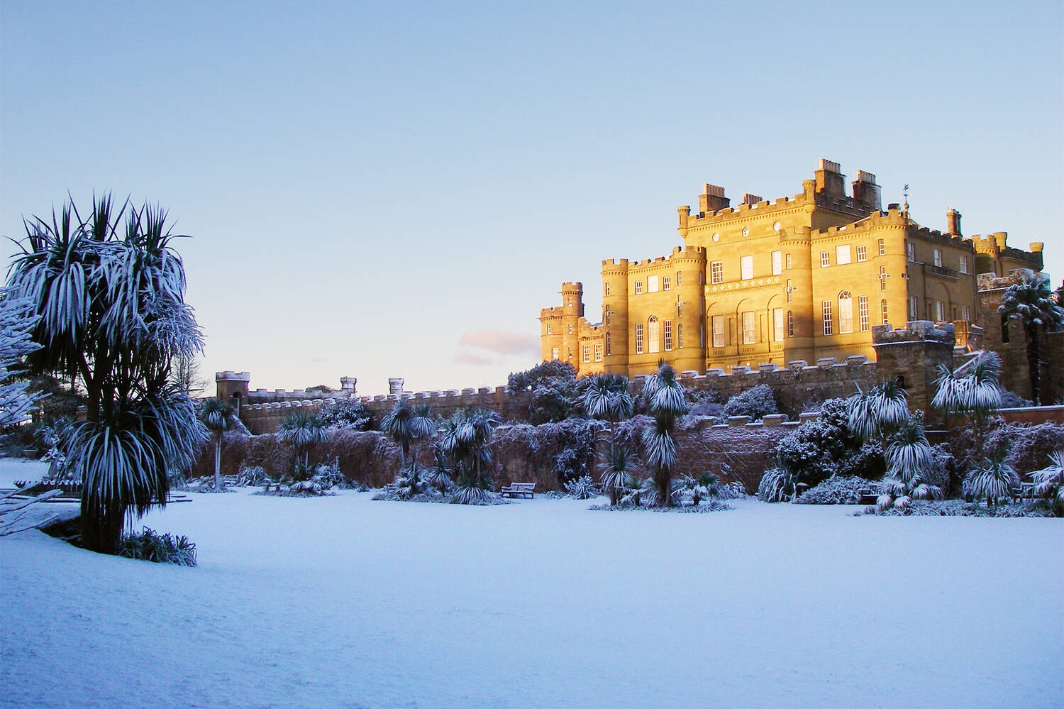 Culzean Castle & Country Park in the snow. To the right of the photo, the east face of the castle is lit by the sun. In the foreground snow covers the flat lawns of the Fountain Court, surrounded by snow-covered palm trees and benches.