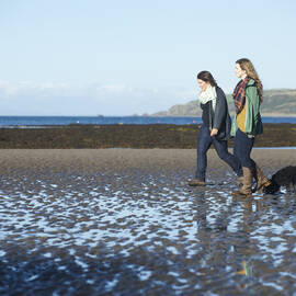 Two women walking along a beach with the tide out, with a black dog walking behind them.