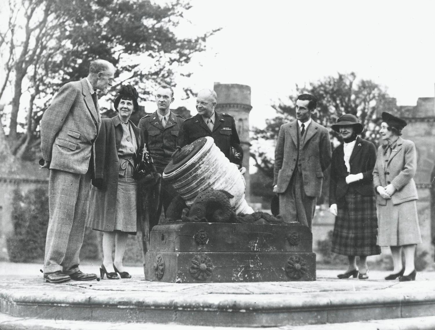 A black and white photograph of a group of people standing around a large cannon at a castle.