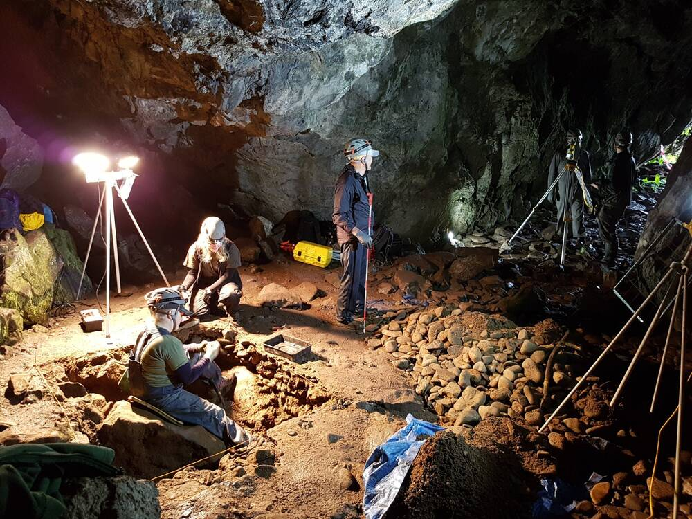 A group of people stand or kneel in a cave, lit by lights on tripods. A square trench has been dug in the middle of the cave floor, and a person sits inside this.