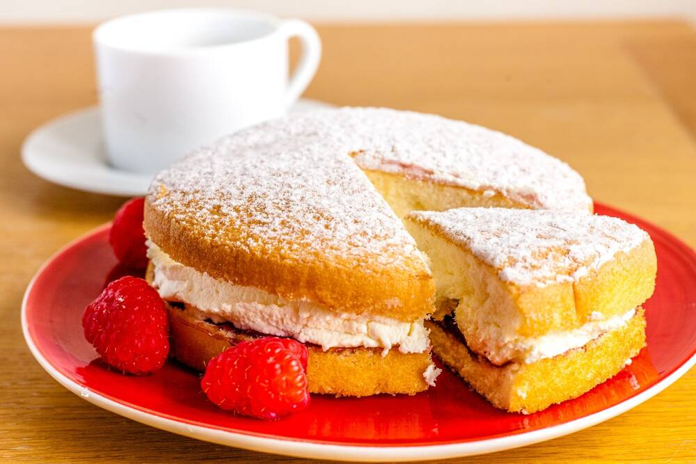 A Victoria sponge sits on a red plate, with raspberries on the side. A cup and saucer stand in the background.
