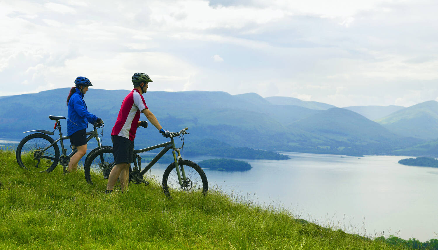 Couple cycling on a hill with view across mountains and loch