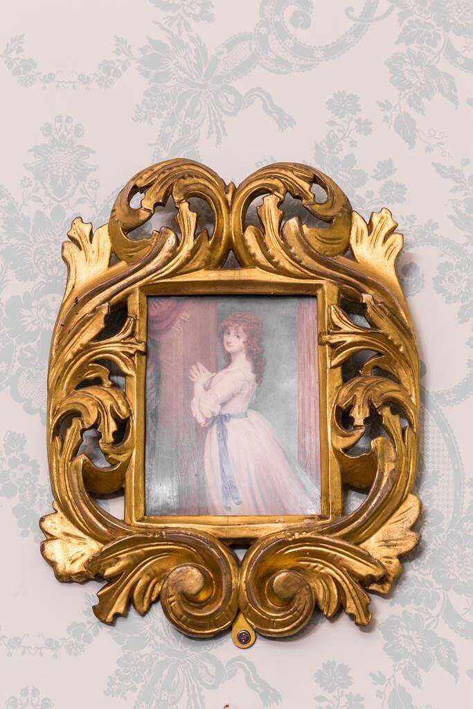 A painting of a woman, hands clasped, looking over her shoulder, wearing a white gown with blue ribbon around her waist. Her red hair, in ringlets, flows over her shoulders. The painting sits in an ornate gold frame and hangs on a wall with patterned paper.