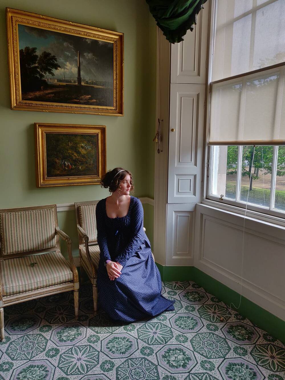 A lady sits in a chair and models a 1800s-style gown as she looks out of the window of a Georgian drawing room.