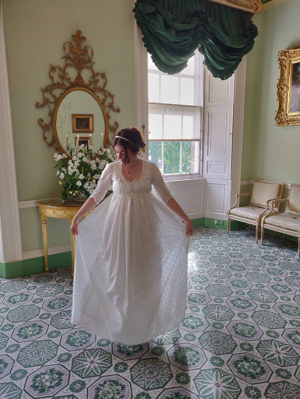 A lady models a white 1800s-style gown in the drawing room of the Georgian House. She holds the skirt out to each side.