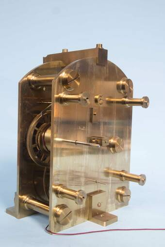 A gleaming brass clock mechanism is displayed against a pale blue background. A thin purple wire runs out from the bottom.