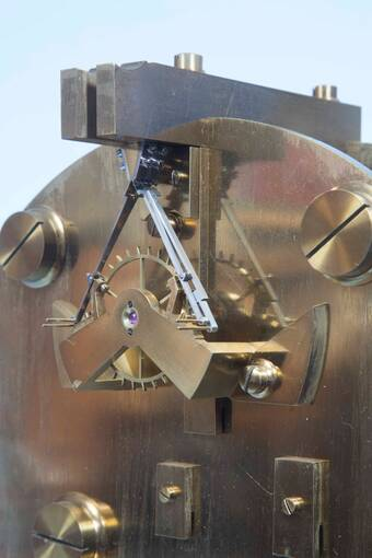 A close-up of a clean clock mechanism, showing a little cog attached to a triangular metal piece.