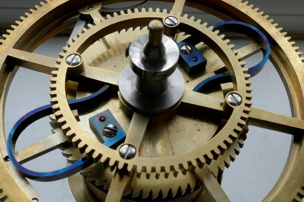A close-up of a clock mechanism, showing a large outer cogged wheel, with a smaller one screwed on top.