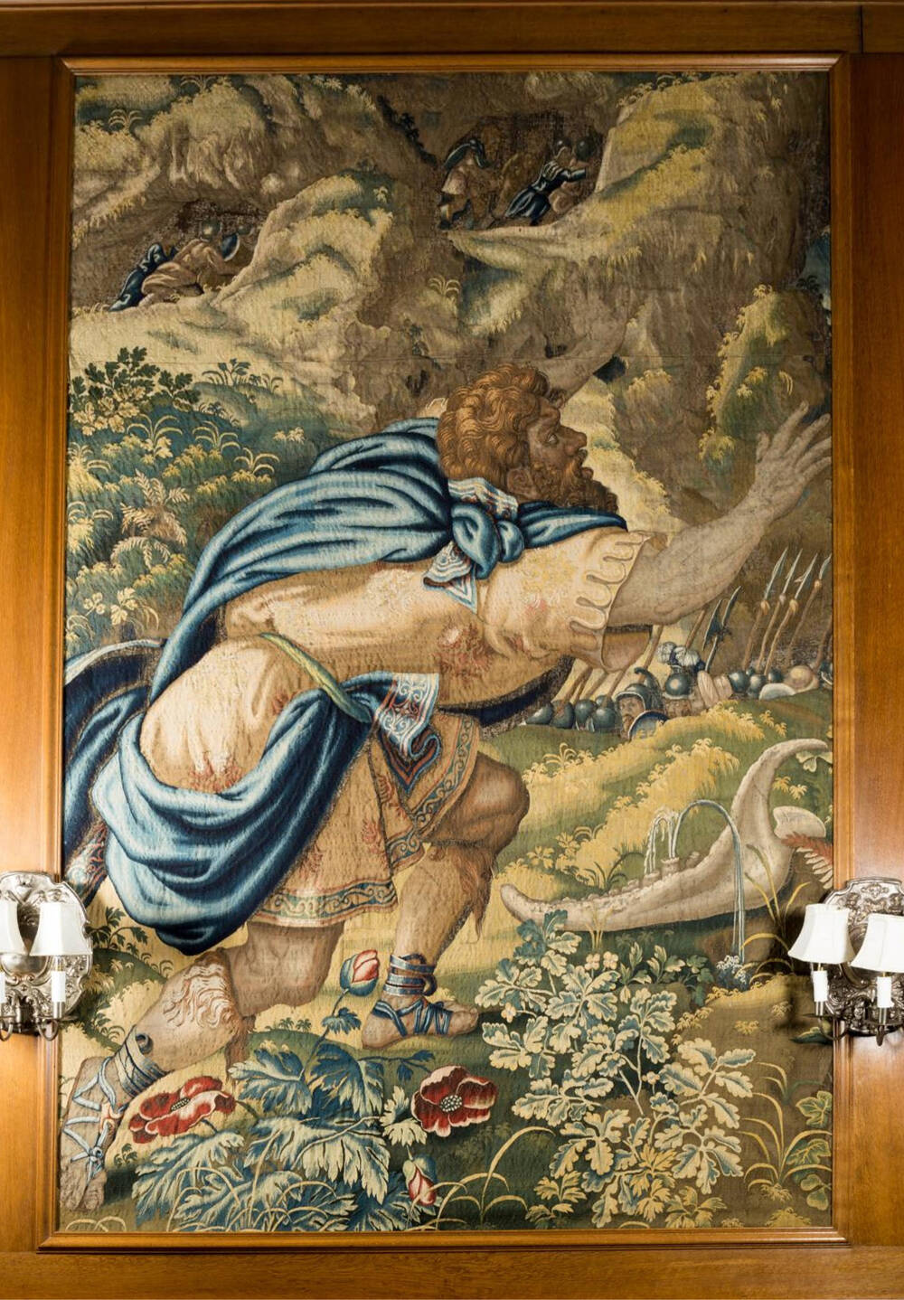A tapestry depicting Samson. He wears a blue wrap and is in a pastoral setting. He is leaning forward.