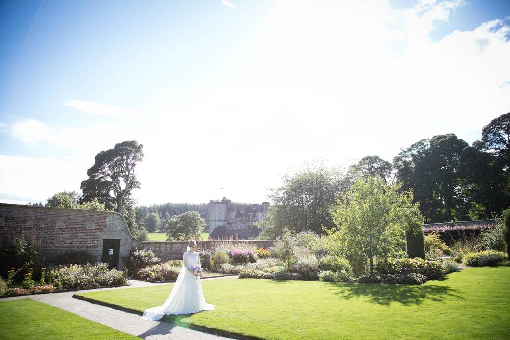 A bride stands in a colourful walled garden, with Castle Fraser in the background. It is a sunny day.