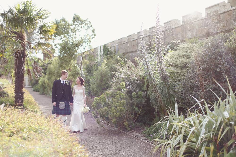 A bride and groom walk arm in hand through the Fountain Court garden at Culzean Castle. A large stone wall runs along the right of the image, and palm trees line the lawn to the left.
