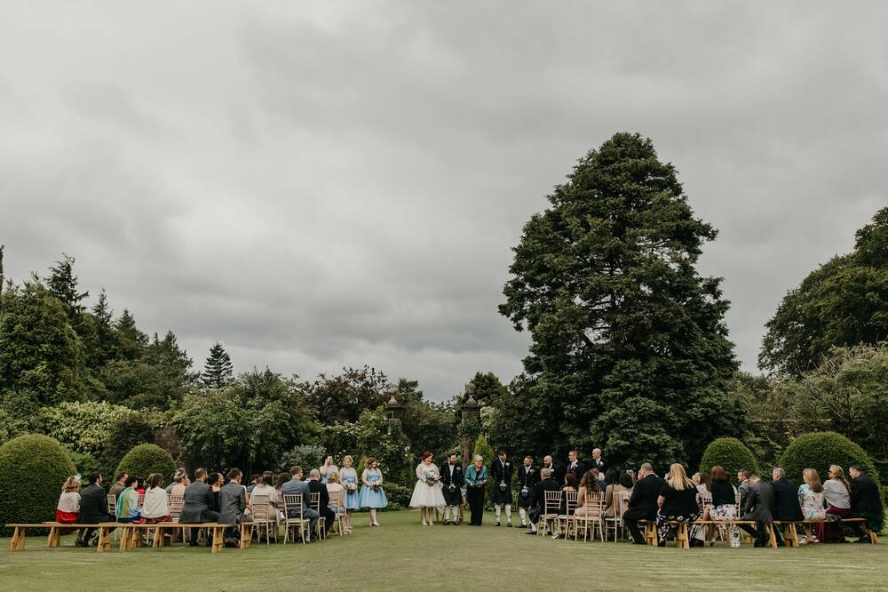 A wedding ceremony taking place at Greenbank Garden. The bride and groom stand at the front with the wedding party, with rows of guests watching on wooden benches. Tall trees stand in the background, behind the ceremony on the manicured lawn.