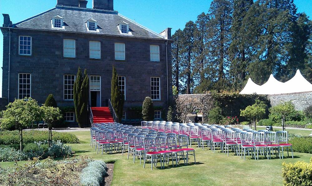A wedding ceremony is set up in the walled garden at House of Dun. Rows of chairs stand on the grass between colourful flower beds. A red carpet runs down the stone stairs from the house into the garden.