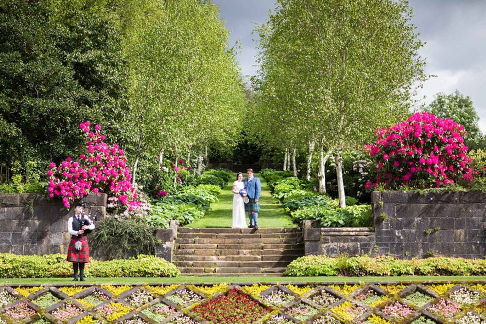 A bride and groom stand at the top of some stair steps, with the colourful and intricate parterre garden at Pollok House in the foreground. A piper plays the bagpipes to the left. An avenue of silver birch trees runs behind.