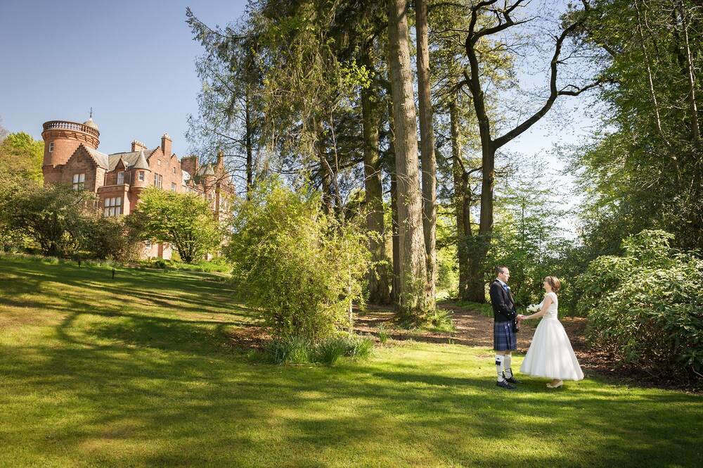 A bride and groom gaze at each other, holding hands, in Threave Garden, with the baronial mansion house in the background. Tall trees are in the background. It is a lovely sunny day with a bright blue sky.